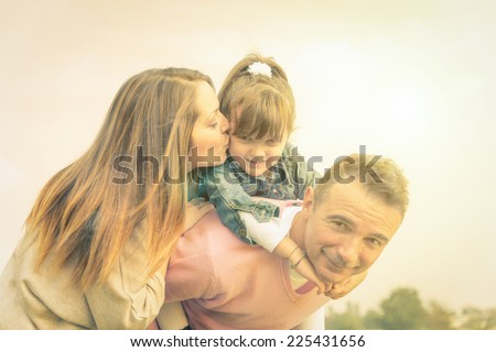 Portrait of happy family - Pretty young girl playing with mama and her father - stock photo