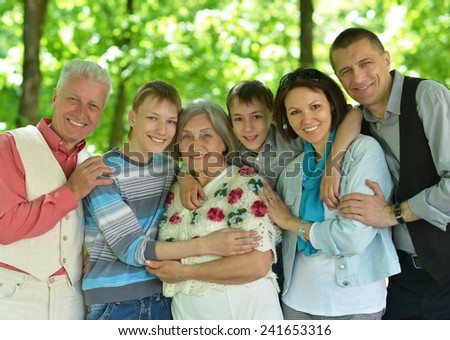 Portrait of happy family resting in park - stock photo