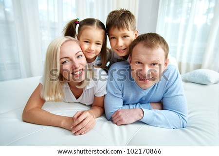 Portrait of happy family resting on bed