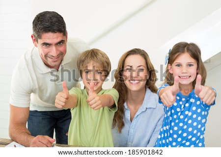 Portrait of happy family showing thumbs up at home - stock photo