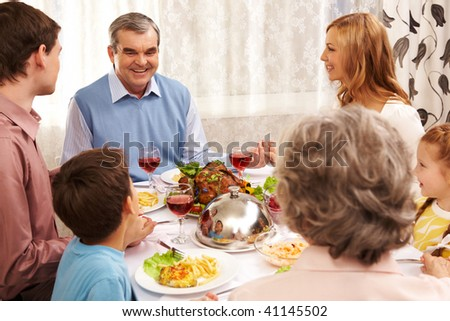 Portrait of happy family sitting at festive table and holding each other by hands - stock photo