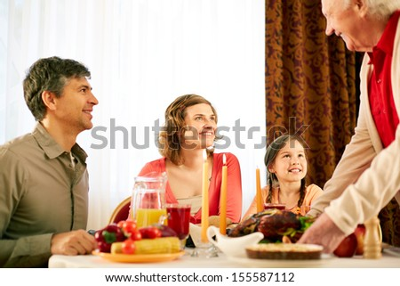 Portrait of happy family sitting at festive table and looking at senior man during Thanksgiving dinner - stock photo