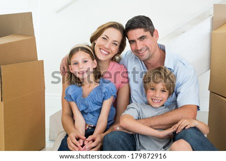 Portrait of happy family sitting in new house - stock photo