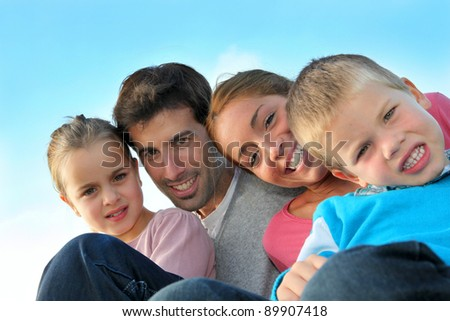 Portrait of happy family sitting outdoors - stock photo