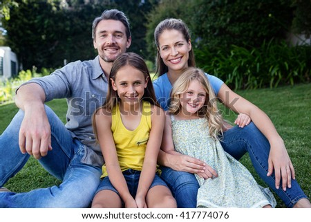 Portrait of happy family sitting together in a garden - stock photo