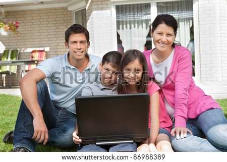 Portrait of happy family sitting together in backyard with laptop