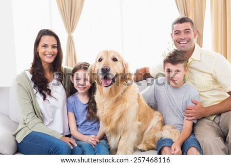 Portrait of happy family sitting with Golden Retriever on sofa at home - stock photo