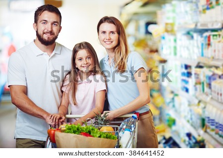 Portrait of happy family standing in supermarket - stock photo