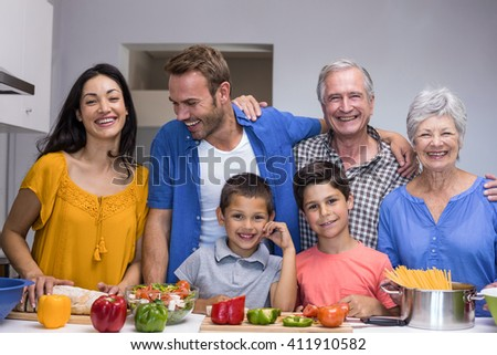 Portrait of happy family standing in the kitchen at home - stock photo