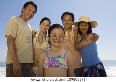 Portrait of happy family standing together on beach - stock photo