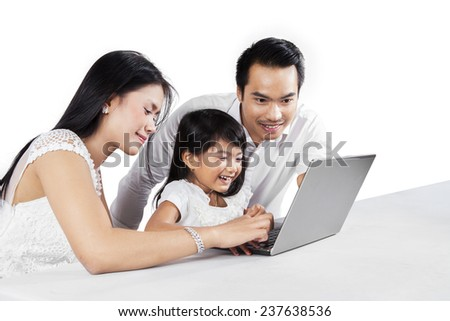 Portrait of happy family using laptop computer together on the table, isolated on white background - stock photo