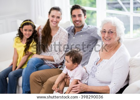 Portrait of happy family with baby while sitting on sofa at home - stock photo