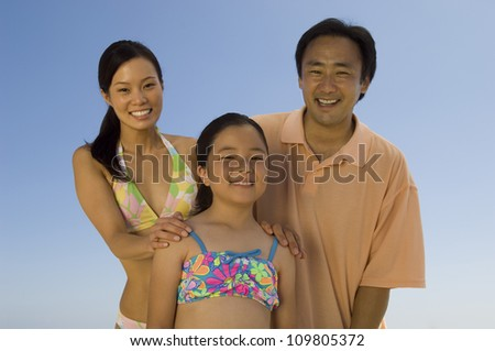 Portrait of happy family with daughter on vacation standing against sky