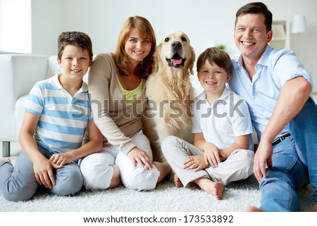 Portrait of happy family with fluffy Labrador having rest at home - stock photo