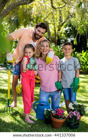 Portrait of happy family with gardening equipment in yard