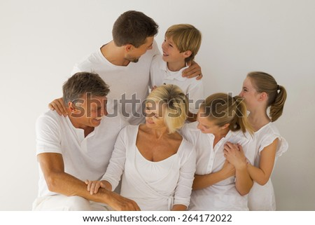 Portrait of happy family with grandparents, parents and grandchildren, looking at each other in a white atmosphere. - stock photo