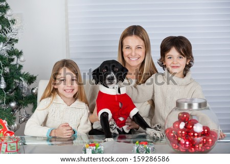 Portrait of happy family with pet dog sitting at home during Christmas - stock photo