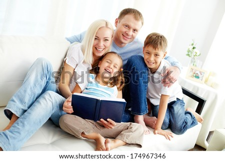 Portrait of happy family with two children looking at camera and laughing  - stock photo