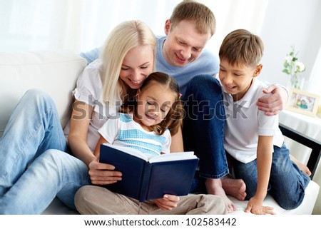 Portrait of happy family with two children reading book - stock photo