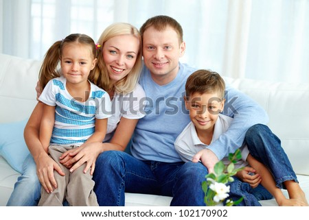 Portrait of happy family with two children sitting at home - stock photo