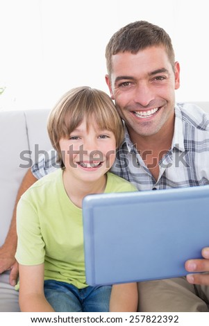 Portrait of happy father and son with digital tablet at home - stock photo