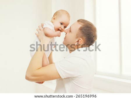 Portrait of happy father holding on hands his baby at home  - stock photo