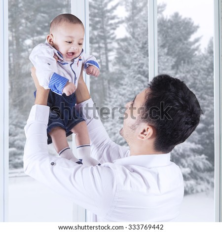 Portrait of happy father lifting up his little son at home, shot with winter background on the window - stock photo