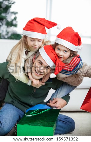 Portrait of happy father piggybacking children during Christmas at home