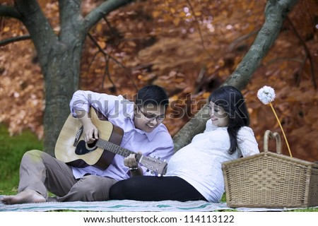 Portrait of happy father playing guitar for his unborn baby on autumn day - stock photo