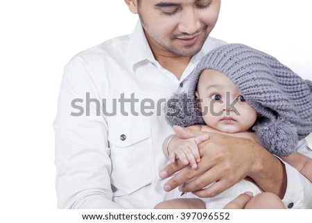 Portrait of happy father standing in the studio while holding his baby, isolated on white background - stock photo