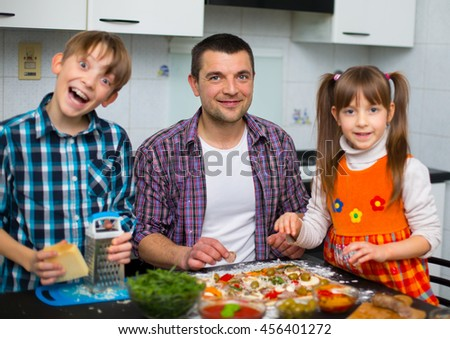 Portrait of happy father with children eating pizza