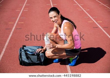 Portrait of happy female athlete with her sports accessories on running track - stock photo