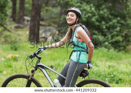 Portrait of happy female biker on field in forest