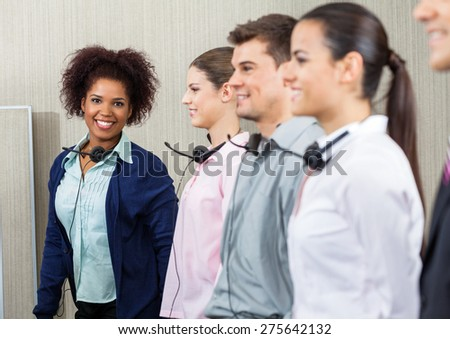 Portrait of happy female call center employee standing with team at call center - stock photo