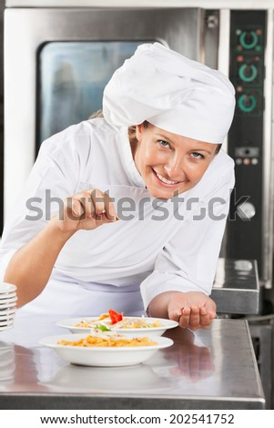 Portrait of happy female chef adding spices to dish at commercial kitchen counter - stock photo