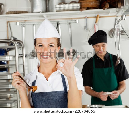 Portrait of happy female chef gesturing okay sign with colleague in background - stock photo