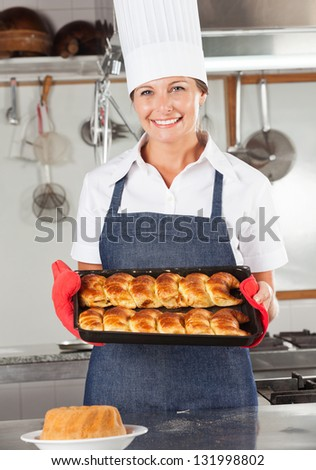 Portrait of happy female chef holding baked bread in restaurant kitchen - stock photo