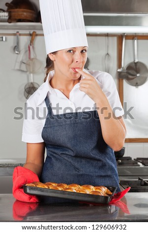 Portrait of happy female chef licking finger while holding bread tray in kitchen - stock photo