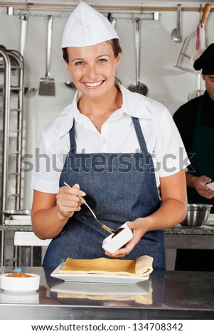 Portrait of happy female chef preparing chocolate roll with colleague in background - stock photo