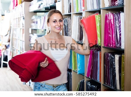 portrait of happy female customer choosing tablecloths in home textile section in shop
