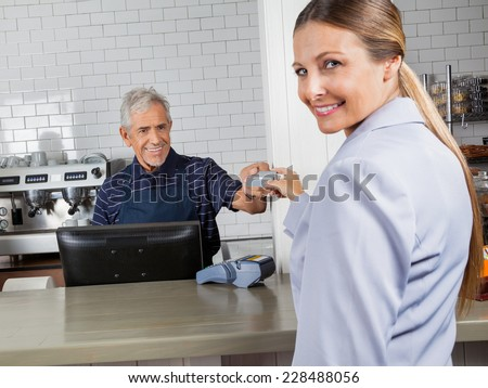 Portrait of happy female customer making payment through credit card at cash counter in grocery store