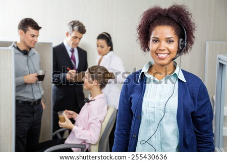 Portrait of happy female customer service representative wearing headphones while team discussing in background at call center - stock photo