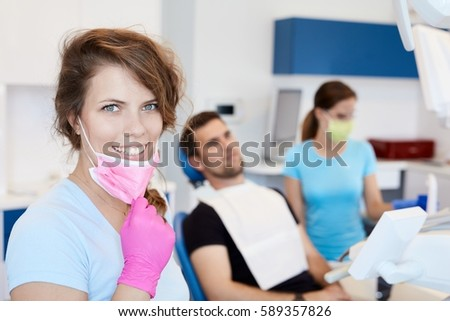 Portrait of happy female dental surgeon smiling, looking at camera.