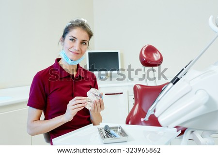 Portrait of happy female dentist in clinic
