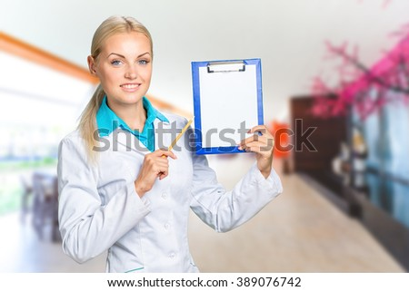 Portrait of happy female doctor holding blank paper on clipboard