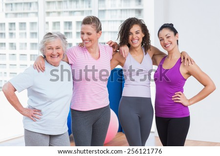 Portrait of happy female friends standing arms around in fitness studio - stock photo