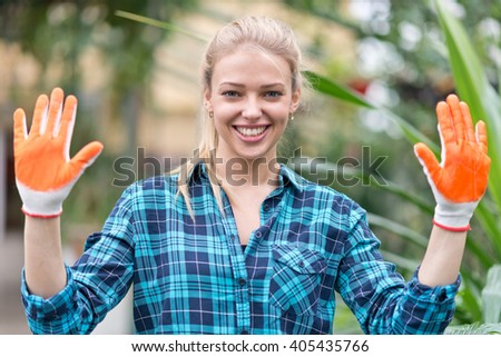 portrait of happy female gardener in greenhouse - stock photo