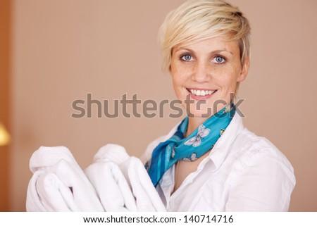 Portrait of happy female housekeeper with bathrobes - stock photo