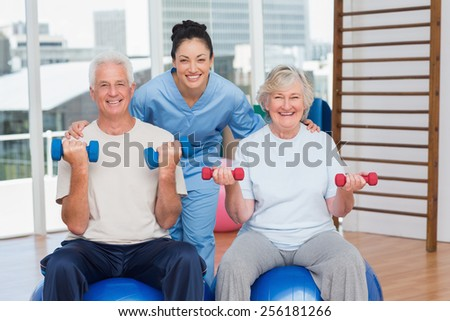 Portrait of happy female instructor with arms around senior couple in gym - stock photo