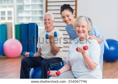 Portrait of happy female instructor with senior couple in gym - stock photo